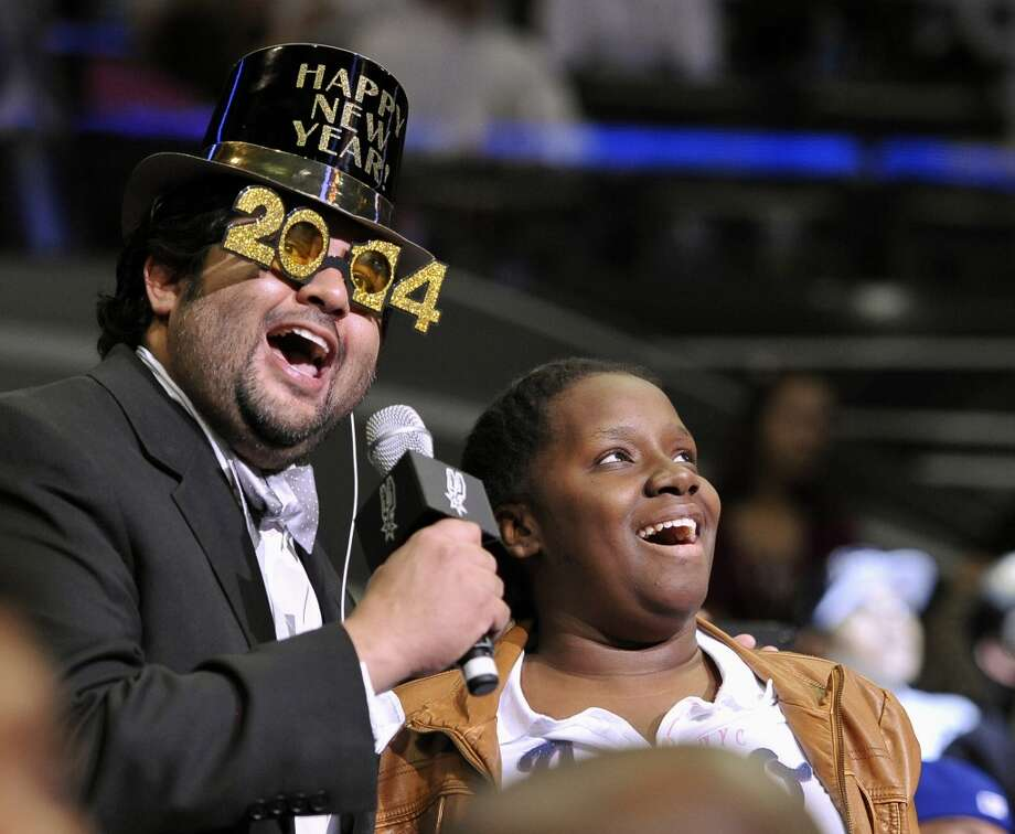San Antonio Spurs emcee J.C. Carpenter, left, talks with a fan during the second half of an NBA basketball game against the Brooklyn Nets on Tuesday, Dec. 31, 2013, in San Antonio. San Antonio won 113-92.(AP Photo/Darren Abate) Photo: Associated Press