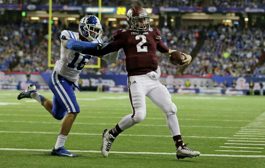 Texas A&M quarterback Johnny Manziel (2) scores a touchdown as Duke safety Jeremy Cash (16) defends in the second half of the Chick-fil-A Bowl NCAA college football game Tuesday, Dec. 31, 2013, in Atlanta. (AP Photo/John Bazemore)