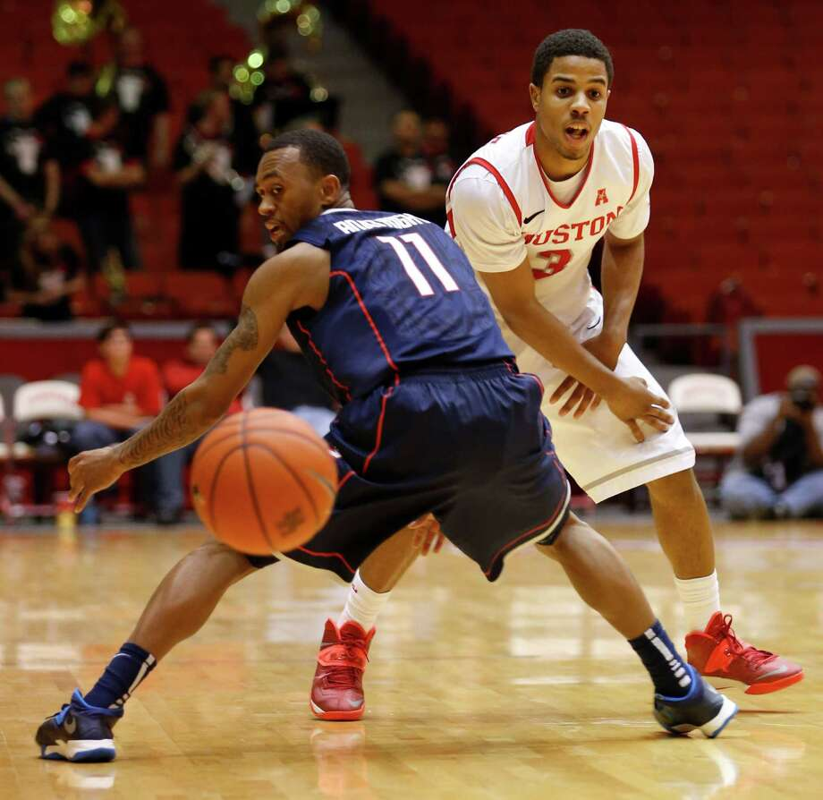 Houston guard Jaaron Simmons (3) passes the ball around Connecticut guard Ryan Boatright (11) in the second half during a basketball game between the University of Houston and the University of Connecticut Dec. 31, 2013 in Houston. Houston won 75-71. Photo: Eric Kayne, For The Chronicle / Eric Kayne