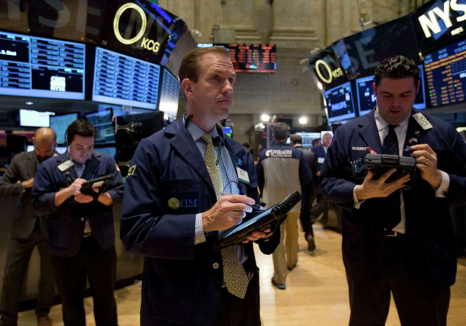 Traders work on the floor of the New York Stock  Exchange Tuesday. The benchmark Standard & Poor's 500 stock index ended the year almost  30 percent higher than it began. Photo: Jin Lee / © 2013 Bloomberg Finance LP