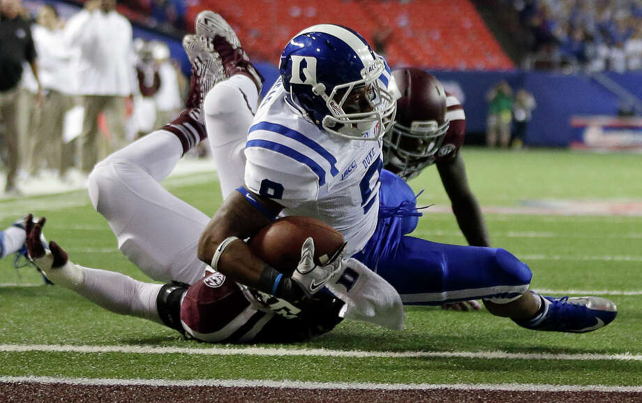 Duke running back Josh Snead (9) scores a touchdown despite the defense of Texas A&M defensive lineman Daeshon Hall (10) in the first half of the Chick-fil-A Bowl NCAA college football game Tuesday, Dec. 31, 2013, in Atlanta. (AP Photo/John Bazemore) Photo: John Bazemore, Associated Press / AP