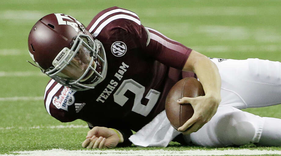 Texas A&M quarterback Johnny Manziel (2) lies on the ground after being sacked in the first half of the Chick-fil-A Bowl NCAA college football game against Duke Tuesday, Dec. 31, 2013, in Atlanta. (AP Photo/John Bazemore) Photo: John Bazemore, Associated Press / AP