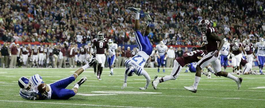 Duke wide receiver Johnell Barnes (4) makes a catch as wide receiver Issac Blakeney (17) flips through the air as Texas A&M defensive back Clay Honeycutt, right, defends in the second half of the Chick-fil-A Bowl NCAA college football game Tuesday, Dec. 31, 2013, in Atlanta. (AP Photo/John Bazemore) Photo: John Bazemore, Associated Press / AP