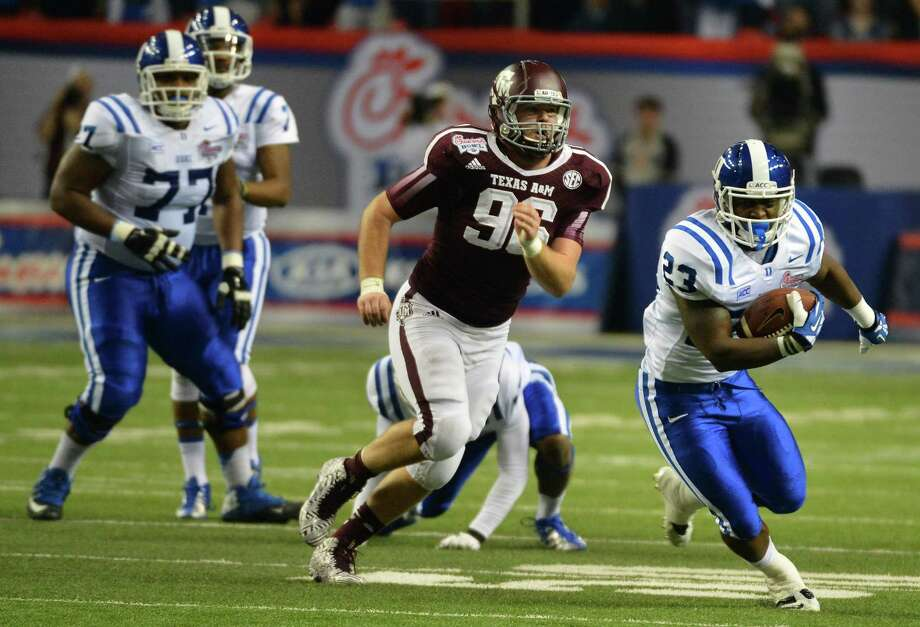 Duke Blue Devils running back Juwan Thompson (23) gets past Texas A&M Aggies defensive lineman Jay Arnold (96) for a first down during the second quarter in the Chick-fil-A Bowl at the Georgia Dome in Atlanta on Tuesday, Dec. 31, 2013. (Chuck Liddy/Raleigh News & Observer/MCT) Photo: Chuck Liddy, McClatchy-Tribune News Service / Raleigh News & Observer