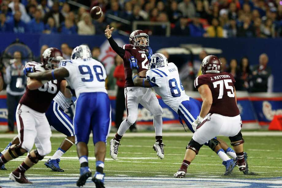 ATLANTA, GA - DECEMBER 31: Johnny Manziel #2 of the Texas A&M Aggies passes the ball as he is hit by Kenny Anunike #84 of the Duke Blue Devils in the first half of the Chick-fil-A Bowl at the Georgia Dome on December 31, 2013 in Atlanta, Georgia. Photo: Joe Robbins, Getty Images / 2013 Getty Images
