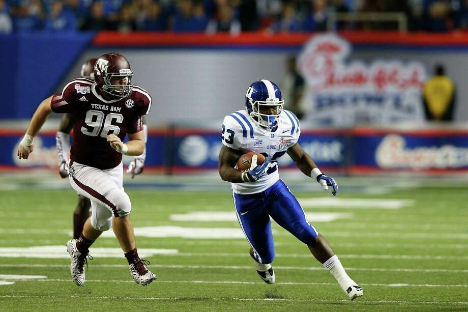 ATLANTA, GA - DECEMBER 31: Juwan Thompson #23 of the Duke Blue Devils rushes for a first down on fourth down in the second quarter against the Texas A&M Aggies during the Chick-fil-A Bowl at the Georgia Dome on December 31, 2013 in Atlanta, Georgia. Photo: Joe Robbins, Getty Images / 2013 Getty Images