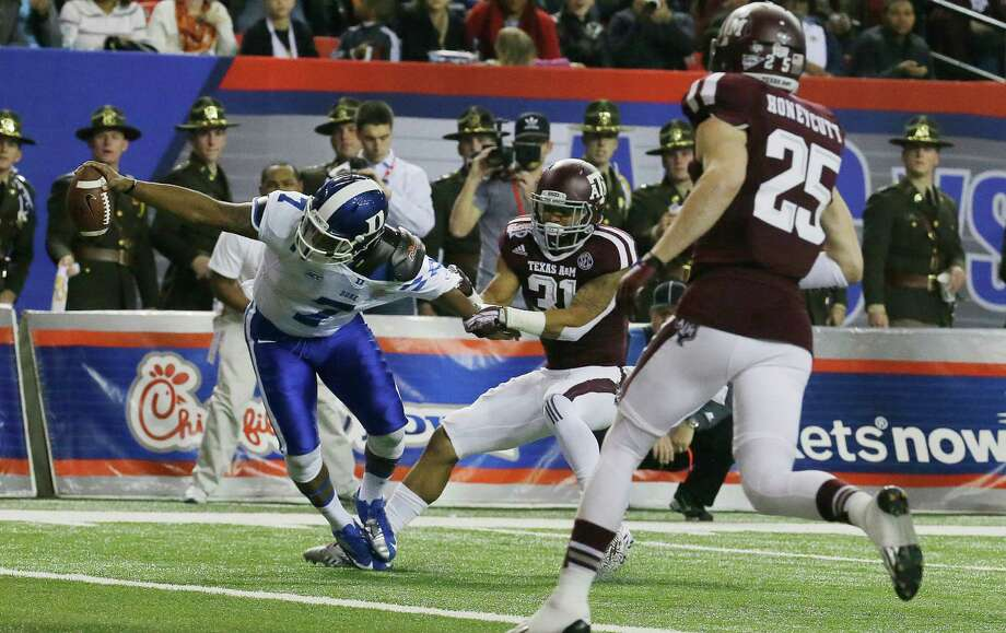 Duke quarterback Anthony Boone (7) pulls out of the tackle of Texas A&M defensive back Howard Matthews (31) on a touchdown run in the first half of the Chick-fil-A Bowl NCAA college football game Tuesday, Dec. 31, 2013, in Atlanta. (AP Photo/Jamie Martin) Photo: Jamie Martin, Associated Press / FR170235 AP