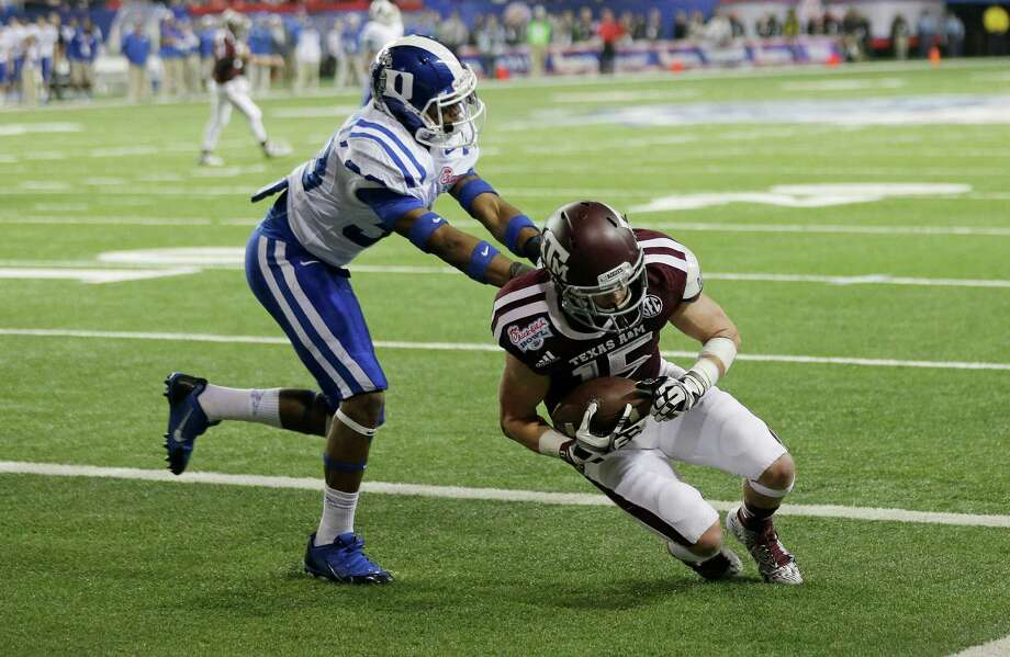Texas A&M wide receiver Travis Labhart (15) scores as Duke cornerback Deondre Singleton (33) defends in the first half of the Chick-fil-A Bowl NCAA college football game Tuesday, Dec. 31, 2013, in Atlanta. (AP Photo/John Bazemore) Photo: John Bazemore, Associated Press / AP