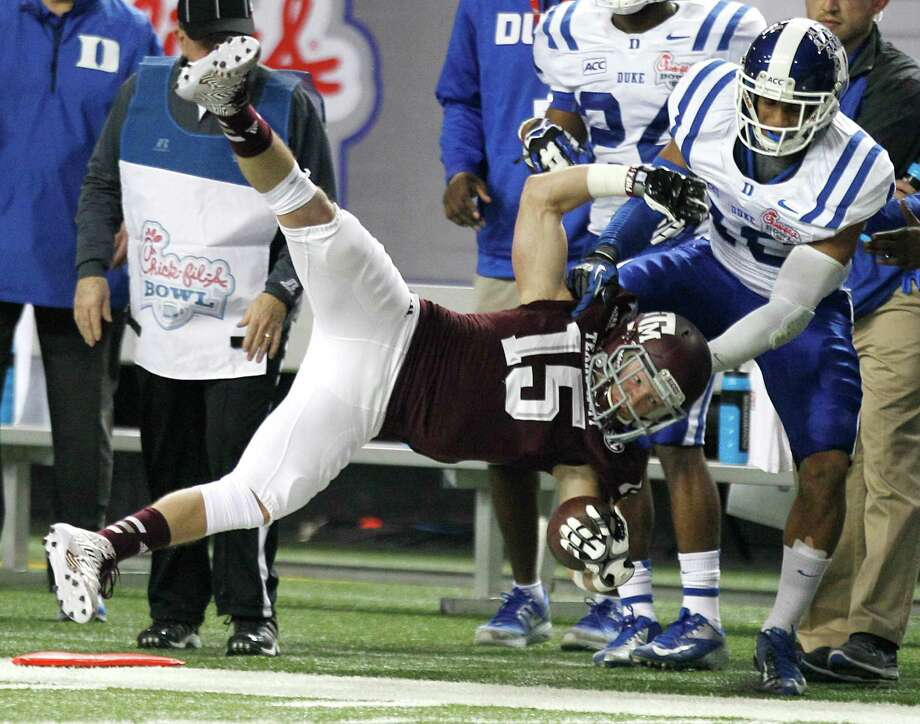 Texas A&M receiver Travis Labhart, who had three TD catches, goes head over heels as he's dragged out of bounds by Duke safety Jeremy Cash on Tuesday night. The Aggies made the game a topsy-turvy affair in the second half, when they rallied from 38-17 down to win. Photo: Brett Coomer, Staff / © 2013  Houston Chronicle