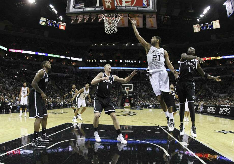 Tim Duncan (21) lays in the ball as Kevin Garnett watches. Garnett failed to make a field goal for the first time since 1996. Photo: Kin Man Hui / San Antonio Express-News / ©2013 San Antonio Express-News