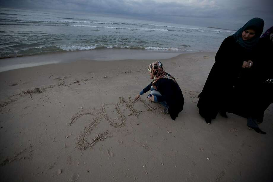 Palestinian girl write in the sand 2014 during the last sunset of the year in Gaza City on December 31, 2013.     TOPSHOTS/AFP PHOTO/MOHAMMED ABEDMOHAMMED ABED/AFP/Getty Images Photo: Mohammed Abed, AFP/Getty Images