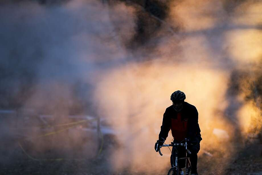 A cyclist passes by vented steam early Tuesday, Dec. 31, 2013, in Philadelphia. (AP Photo/Matt Rourke) Photo: Matt Rourke, Associated Press