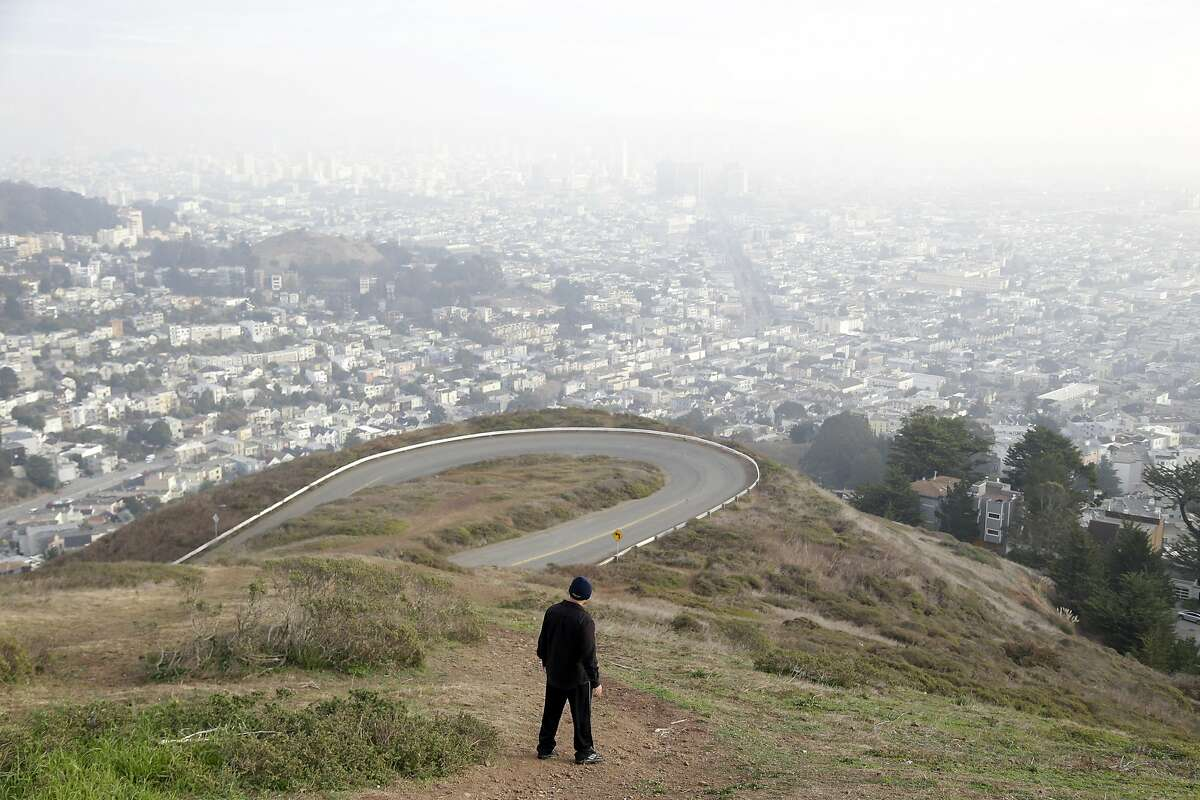 A visitor hikes down a pathway overlooking the skyline on Twin Peaks on Tuesday, Dec. 31, 2013, in San Francisco. Twin Peaks is among the places on the Peak2Peak hike. (AP Photo/Marcio Jose Sanchez)