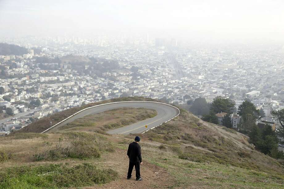 A visitor hikes down a pathway overlooking the skyline on Twin Peaks on Tuesday, Dec. 31, 2013, in San Francisco. (AP Photo/Marcio Jose Sanchez) Photo: Marcio Jose Sanchez, Associated Press