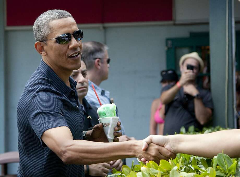 President Barack Obama shakes hands with people waiting to meet him as he holds his shave ice outside Island Snow, Tuesday, Dec. 31, 2014. The first family is in Hawaii for their annual holiday vacation. (AP Photo/Carolyn Kaster) Photo: Carolyn Kaster, Associated Press