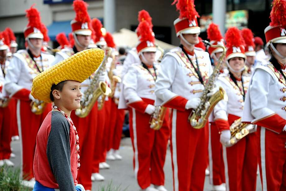 Nebraska fan Cruz Kirwan, 10, San Antonio, crosses the street to get closer to the Cornhusker Marching Band Tuesday, Dec. 31, 2013 in Jacksonville, Fla. The Gator Bowl Parade, presented by Republic Services, of floats, bands, cars and clowns snaked through Downtown for Georgia and Nebraska fans. (AP Photo/Florida Times-Union/Bruce Lipsky) Photo: Bruce Lipsky, Associated Press