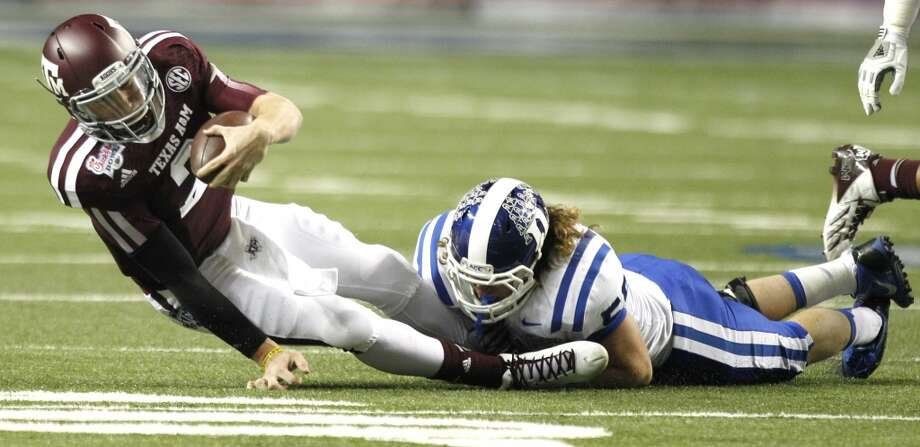 A Duke defender wraps up Texas A&M quarterback Johnny Manziel. Photo: Brett Coomer, Houston Chronicle