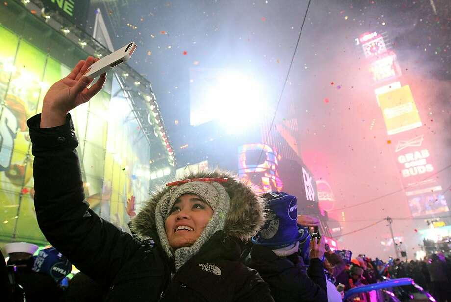 Taya Charoenth, of Bangkok, Thailand captures the scene in New York's Times Square shortly after midnight New Year's Day Wednesday Jan. 1, 2014, in New York. Photo: Tina Fineberg, Associated Press
