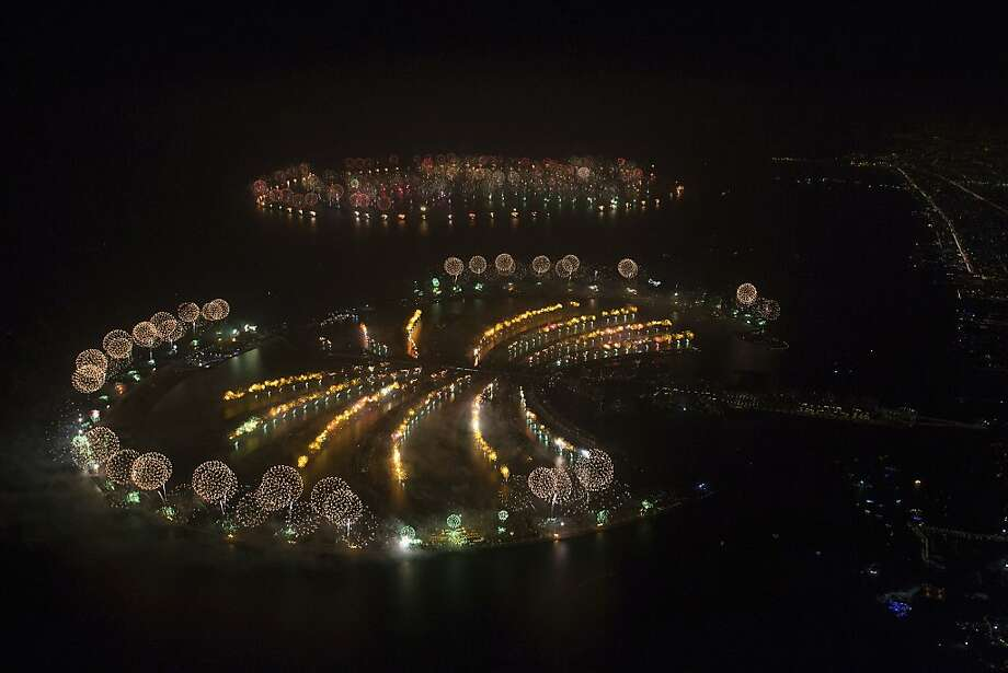 """In this photo provided by Dubai World Record 2014, fireworks explode over Palm Jumeirah Island, front, and World Islands, rear, to celebrate the New Year on Wednesday, Jan. 1, 2014 as the city attempts to breaks the Guinness World Record for the """"Largest Firework Display."""" Photo: Simon Brooke-Webb, Associated Press"""