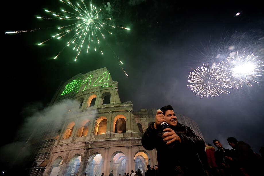 People celebrate the new year by the ancient Coliseum in Rome on January 1, 2014. Photo: FILIPPO MONTEFORTE, AFP/Getty Images / 2014 AFP