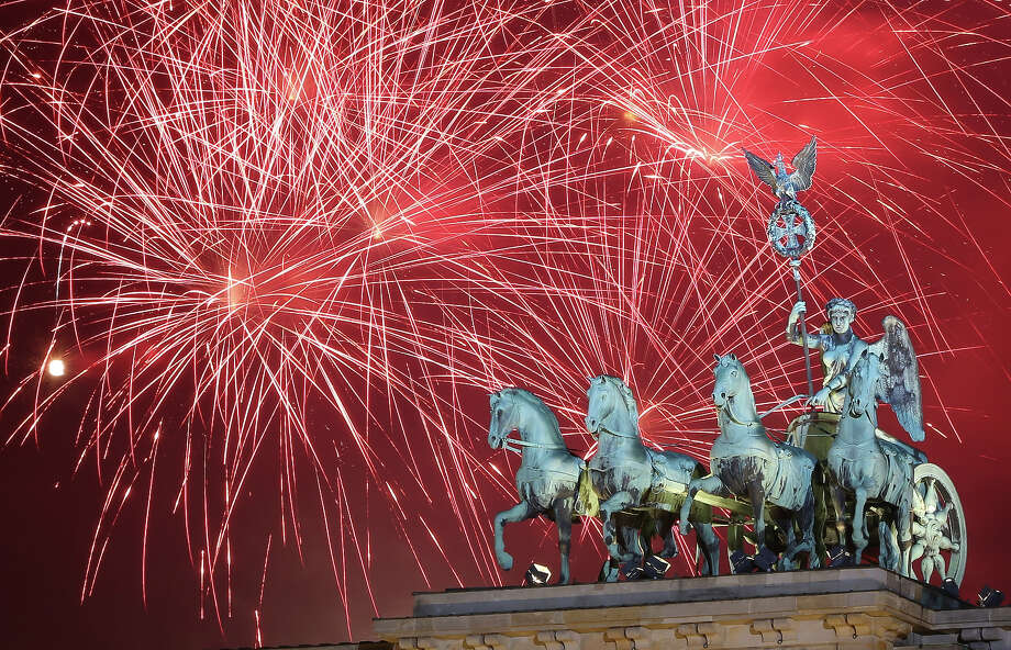 Fireworks explode behind the Quadriga statue on top of the Brandenburg Gate shortly after midnight on January 1, 2014 in Berlin, Germany. Tens of thousands of revelers gathered in the city center to celebrate New Year's Eve. Photo: Adam Berry, Getty Images / 2014 Getty Images