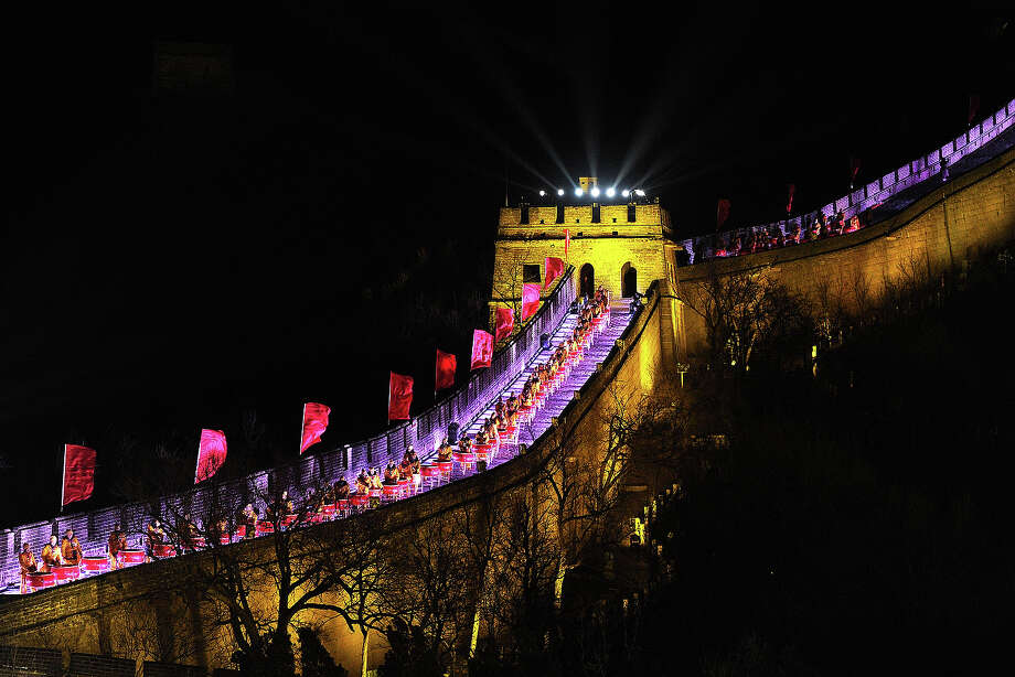 People dressed in traditional costumes play drums during a performance to celebrate the new year at the Great wall in Beijing on December 31,2013.  Hundreds of people gathered at the Great Wall, a landmark place in Beijing, to celebrate the New Year. Photo: WANG ZHAO, AFP/Getty Images / 2013 AFP