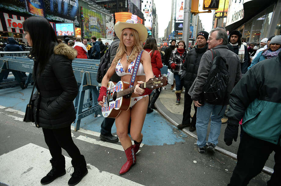 The Naked Cowgirl walks up Broadway on December 31, 2013 at Times Square in New York. Cold temperatures are forecast as the crowd is expected to reach one million to watch the New Year ball to drop. Photo: DON EMMERT, AFP/Getty Images / 2013 AFP