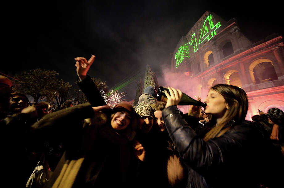 People cheer by the ancient Coliseum to celebrate the new year in Rome on January 1, 2014. Photo: FILIPPO MONTEFORTE, AFP/Getty Images / 2014 AFP
