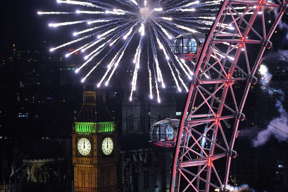 Fireworks explode above the Houses of Parliament and the London Eye during the New Year celebrations in central London just after midnight on January 1, 2014. Photo: LEON NEAL, AFP/Getty Images / 2014 AFP