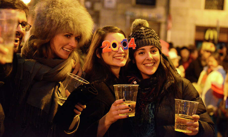 People enjoy a drink in Puerta del Sol in Madrid on December 31, 2013 during New Year celebrations. Photo: GERARD JULIEN, AFP/Getty Images / 2014 AFP