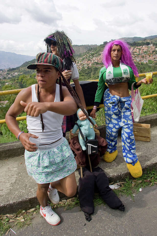 "Young men dressed as women ask for money to passing drivers in Medellin, Colombia, on December 31, 2013. It is a Colombian tradition to burn the so called ""old year dolls"" on December 31 at midnight as a way to left all the bad behind and start a new year in an auspicious way. Photo: FREDY AMARILES, AFP/Getty Images / 2013 AFP"