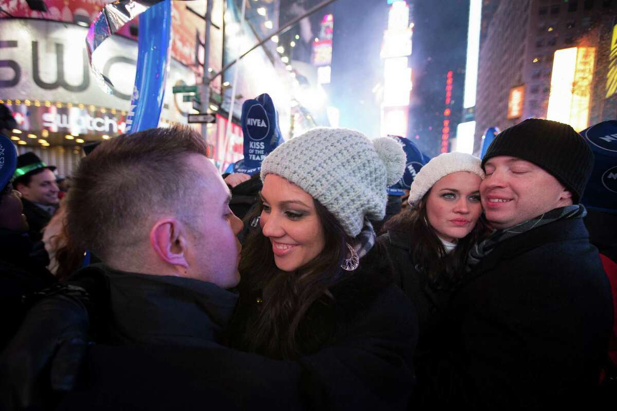 Rob Rudolph, left, and Amanda Weaber, center, smile following a kiss after midnight during the New Year's Eve celebrations in Times Square, Wednesday, Jan. 1, 2014, in New York.