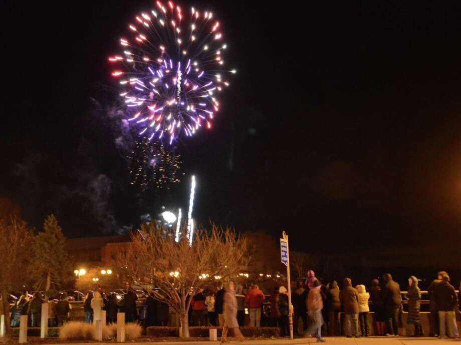 Fireworks light up the sky over Jesup Green as hundreds line the Post Road bridge for the culmination of First Night Westport-Weston on Tuesday night. Photo: Jarret Liotta / Westport News contributed