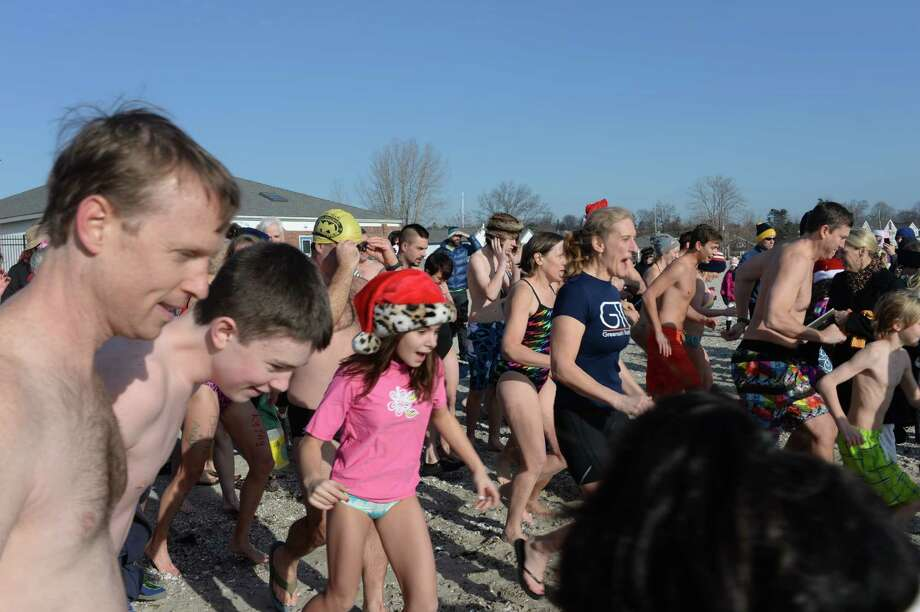 Team Mossman held their 11th annual polar plunge on New Year's Day at Compo Beach in Westport.  The plunge was scheduled for 10 a.m.  The air was brisk and we can only imagine what temperature the water was. All of the donations these divers collect benefit Save the Children.  Save the Children is a charity that helps improve the lives of impoverished children in more than 120 countries around the world.   Photo: Marc Poirier, Marc Poirier / Hearst Connecticut Media Group / Marc Poirier Photograhy