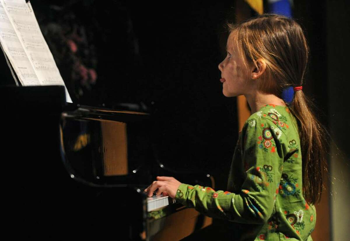 """Osborn Hill Elementary School held its Annual Variety Show at Roger Ludlowe Middle School Auditorium in Fairfield, Conn. on Friday January 29, 2010. Here, Kylee Holderied concentrates as she performs """"Puff the Magic Dragon"""" on piano."""