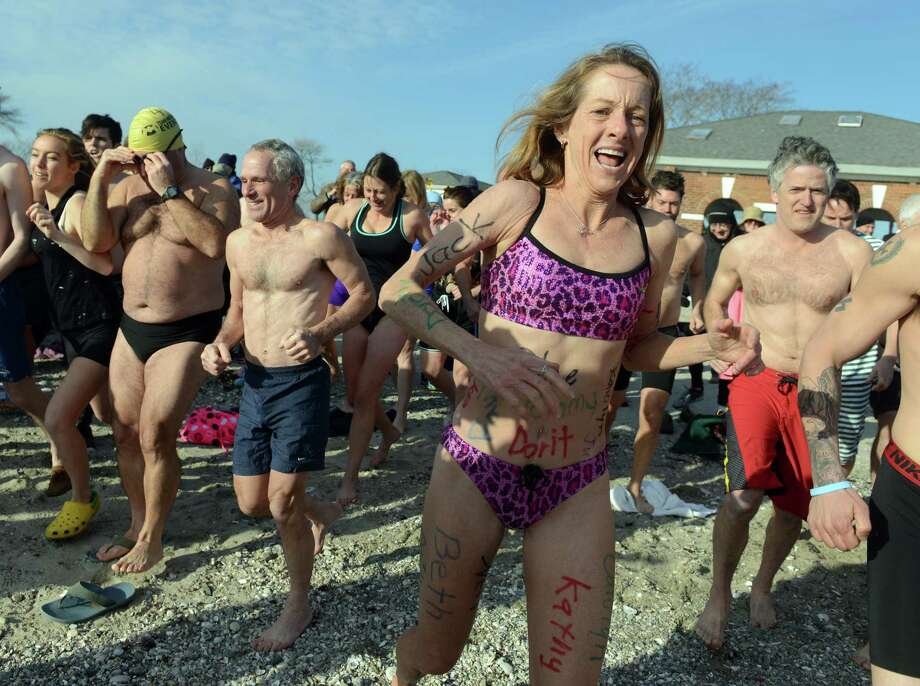 Andrea Williamson, of Norwalk, wears the names of her top donors as she takes the plunge for charity during the 11th Annual Save the Children Mossman Polar Plunge Wednesday, January 1, 2014 at Compo Beach in Westport, Conn. Photo: Autumn Driscoll / Connecticut Post