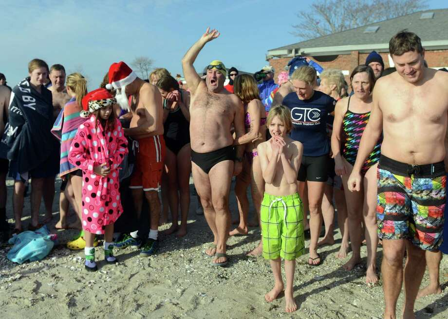 Participants prepare to charge into the Long Island Sound for the 11th Annual Save the Children Mossman Polar Plunge Wednesday, January 1, 2014 at Compo Beach in Westport, Conn. Photo: Autumn Driscoll / Connecticut Post