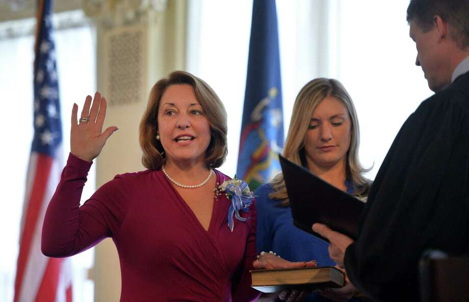Saratoga Springs Mayor Joanne Yepsen is sworn in by Saratoga City Court Judge Jeffrey Wait, right, Wednesday afternoon Jan. 1, 2014 in the Canfield Casino in Saratoga Springs, N.Y.  Holding the Bible is her daughter Emma.      (Skip Dickstein / Times Union) Photo: SKIP DICKSTEIN / 0025223A