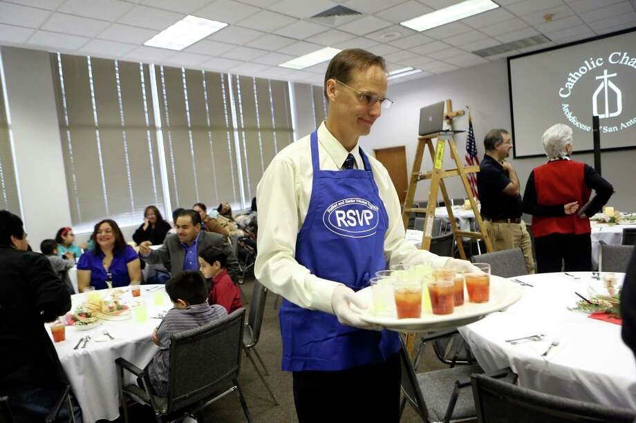 Mitch Finnie serves drinks as Catholic Charities held a special New Year's Day Luncheon for their clients.  Teams of volunteer servers waited on them for the banquet on Wednesday Jan. 1, 2014 Photo: Helen L. Montoya, SAN ANTONIO EXPRESS-NEWS / SAN ANTONIO EXPRESS-NEWS