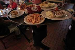 Marivel Wubs carries a tray with dishes including black eyed peas and cabbage at the Black-eyed Pea restaurant in the 4200 block of Bellaire Boulevard Wednesday, Jan. 1, 2014, in Houston.