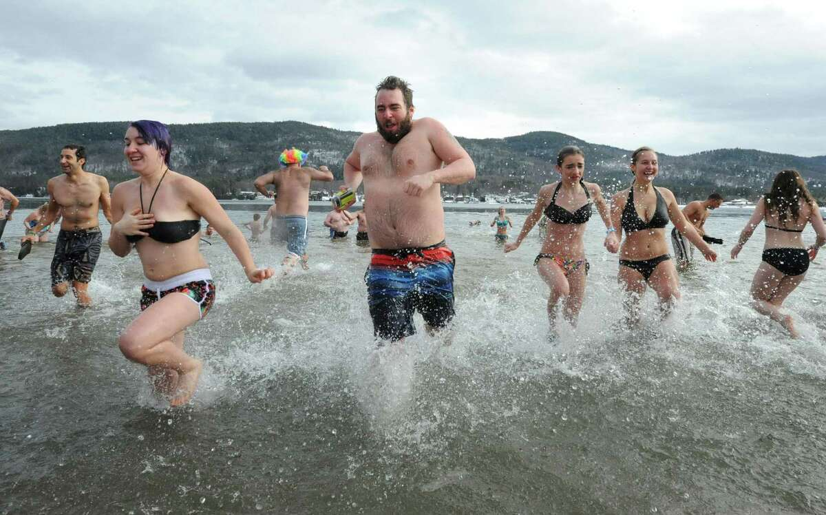 People brave the icy cold water at the annual Lake George Polar Plunge on Wednesday, Jan. 1, 2014 in Lake George, N.Y. The New Year's Day tradition draws hundreds of people to Shepard Park Beach every year. (Lori Van Buren / Times Union)
