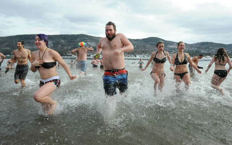 People brave the icy cold water at the annual Lake George Polar Plunge on Wednesday, Jan. 1, 2014 in Lake George, N.Y. The New Year's Day tradition draws hundreds of people to Shepard Park Beach every year. (Lori Van Buren / Times Union) Photo: Lori Van Buren / 00025152A