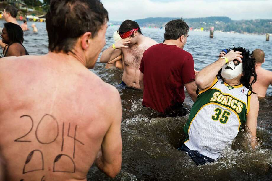 A masked man dunks himself during the 12th Annual Polar Bear Plunge Wednesday, Jan. 1, 2014, at Matthews Beach Park in Seattle. About 300 people participated in the first Polar Bear Plunge in 2003; since then, attendance has nearly reached 1,000 attendees. Photo: JORDAN STEAD, SEATTLEPI.COM / SEATTLEPI.COM