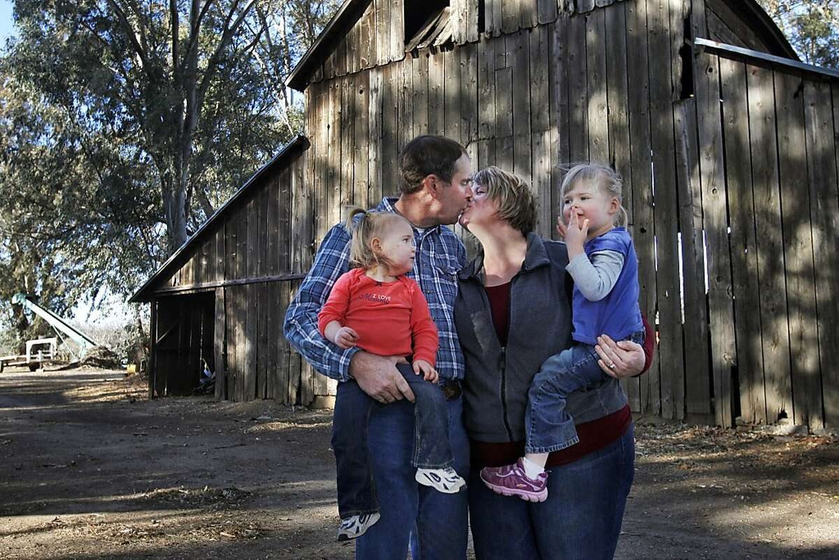 Rebekah and Ken Sullivan pictured with their daughters Ruth, 1, left, and Grace, 3, outside of the oldest barn on their property December 20, 2013 at their home and Almond orchard in Orland, Calif. Ken Sullivan is a fourth generation Almond farmer, the land has been in his family for 100 years. Rebekah always knew she wanted to be a stay-at-home mother and had dreamt of ending up with a farmer. The two have been married for a little over four years now and they have two daughters. Both of them say they feel blessed to have found each other through the dating website, Farmer's Only.