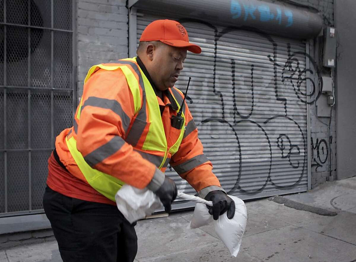 John Dixon seals a bag containing human excrement as the DPW's downtown alley crew cleans the sidewalk on Stevenson Street where the homeless congregate in San Francisco's District 6.