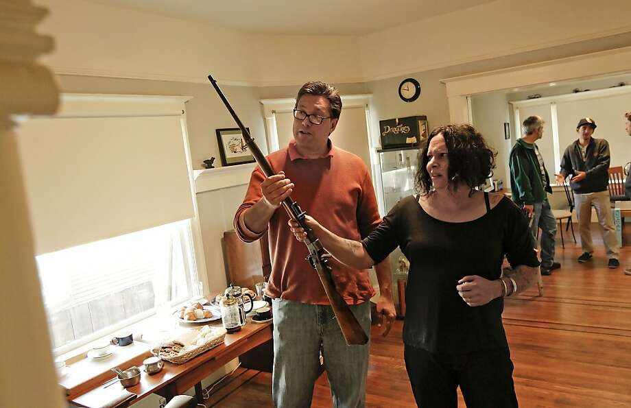 Eric Wooten, a longtime California Democratic Party activist and member of the Liberal Gun Club, checks out an 1889 Swedish Rolling Block rifle with the gun's owner, Marlene Hoeber. Photo: Michael Macor, The Chronicle