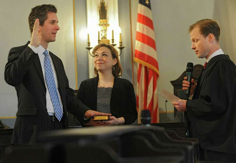 Carl Erikson takes the oath for city council which is administered by Honorable Mark Blanchfield as his wife Justine holds the Bible at Schenectady City Hall on Wednesday, Jan. 1, 2014 in Schenectady, N.Y.  (Lori Van Buren / Times Union) Photo: Lori Van Buren / 00025222A