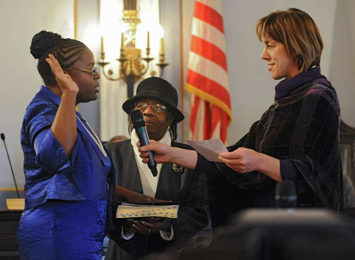 Marion Porterfield takes the oath for city council which is administered by state Sen. Cecilia Tkaczyk as her mother, the Rev. Diana Fletcher, holds the Bible at Schenectady City Hall on Wednesday, Jan. 1, 2014 in Schenectady, N.Y. Fletcher, who was a pastor in Gloversville and active in the Schenectady community, passed away in June 2021. (Lori Van Buren / Times Union)