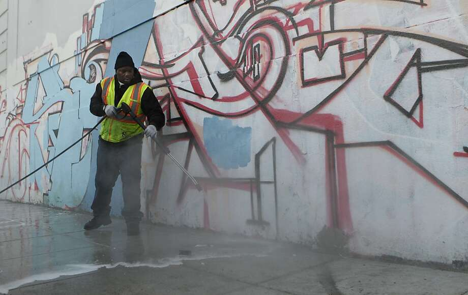Marquez Boyd uses a power washer to spray the sidewalk on Stevenson Street when the Public Works Department's downtown Alley Crew cleaned up where homeless men had spent the night. Photo: Paul Chinn, The Chronicle