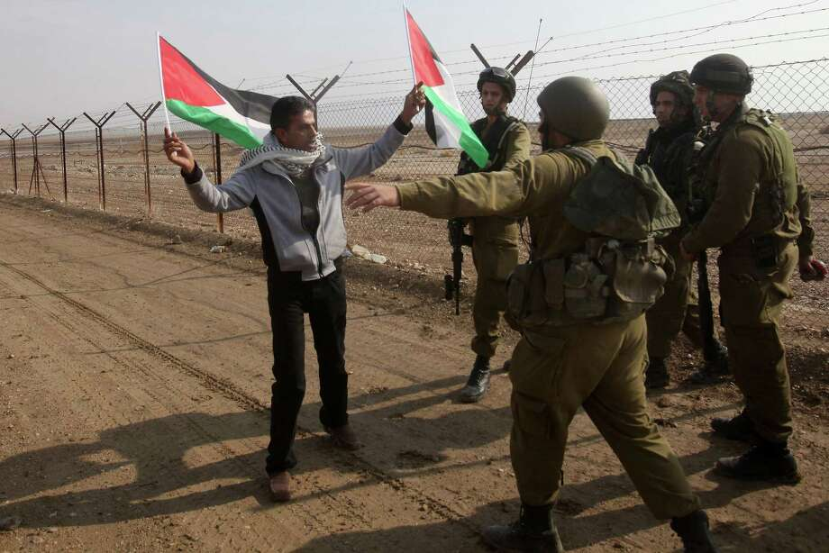 Israeli security forces prevent a Palestinian protester from affixing a Palestinian flag on the Jordanian-Israeli border fence during a rally Wednesday near Jericho. Photo: HAZEM BADER, Stringer / AFP